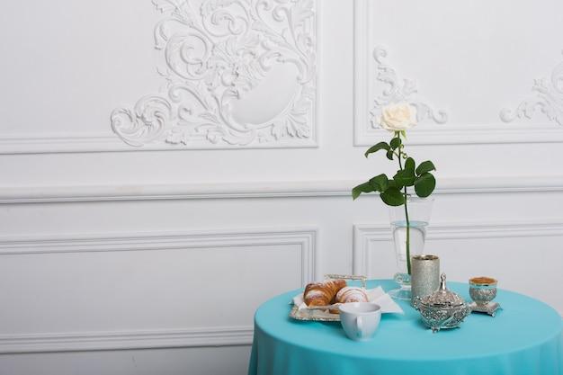 Croissant und weiße rose auf einem tisch gegen luxuswand, kopierraum