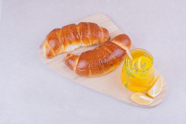 Croissantbrötchen mit einem glas limonade