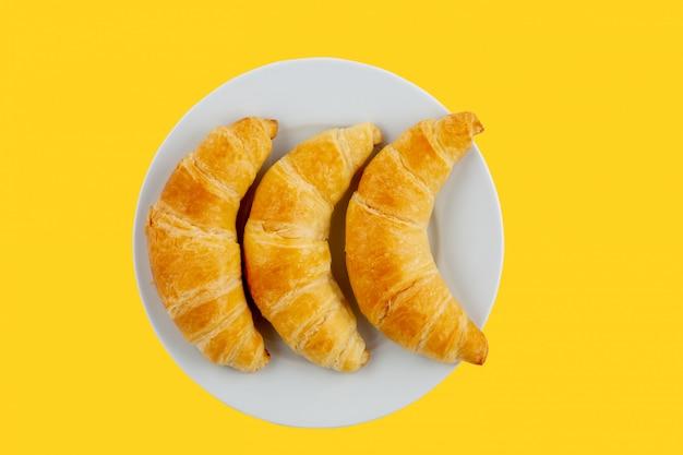 Croissantbrot auf einem weißen teller in einem gelben
