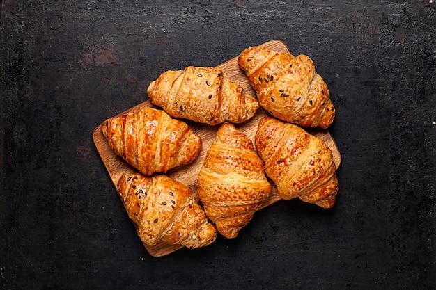 Croissants auf auf holzbrett, das auf altem rustikalem hintergrund liegt