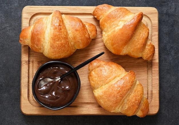 Croissants auf einem holzbrett mit schokoladenpaste. sicht von oben.