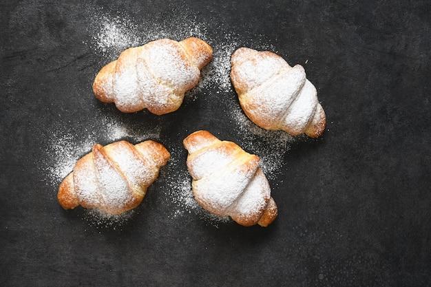Croissants auf einem schwarzen betontisch. sicht von oben.