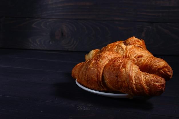 Croissants auf einem teller im dunkeln