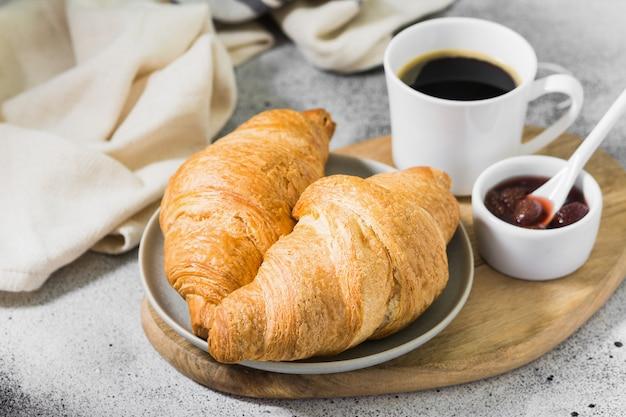 Croissants auf einem teller mit kaffee und erdbeermarmelade. gebäck zum frühstück