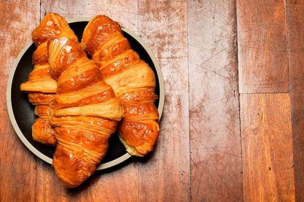 Croissants auf einer schwarzen platte mit einer flachen draufsicht des hölzernen hintergrundes