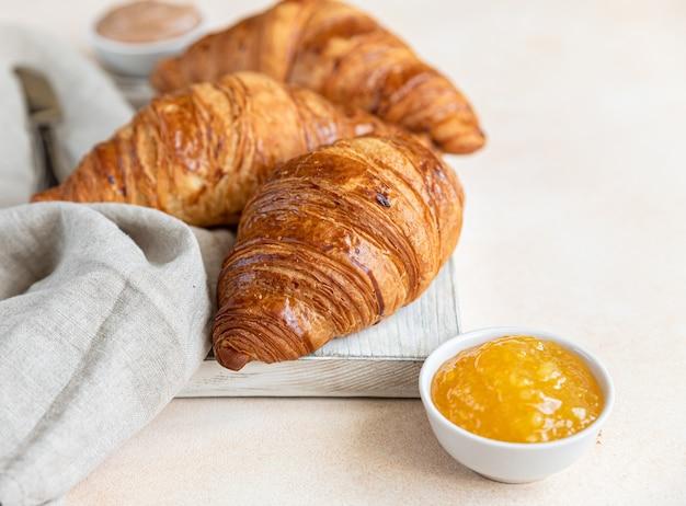 Croissants auf holzschneidebrett mit marmelade und schokoladencreme