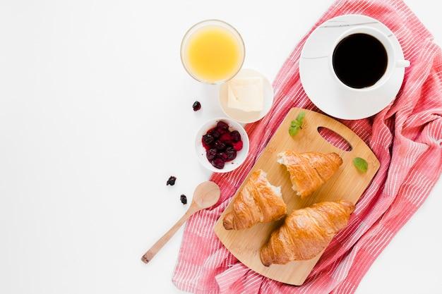 Croissants auf schneidebrett mit kaffee und orangensaft