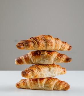 Croissants auf weißem und grauem tisch. seitenansicht.