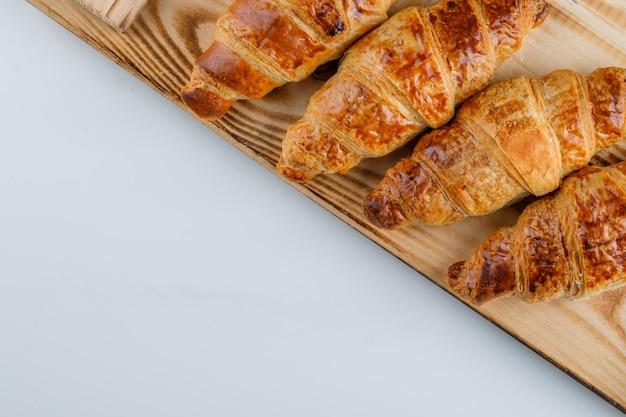 Croissants auf weißem und hölzernem tisch. flach liegen.