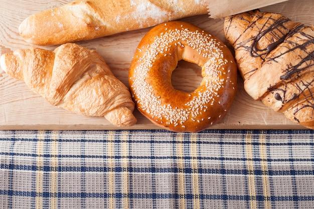 Croissants, französisches baguette und frisches backen auf holztisch