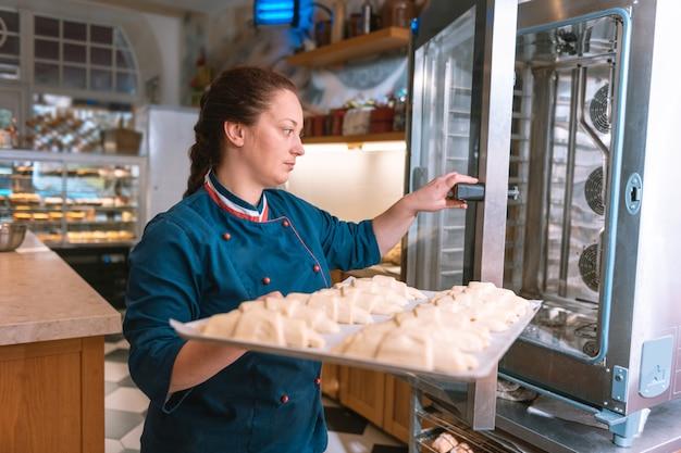 Croissants im ofen. erfahrener französischer bäcker in blauer jacke, der damit beschäftigt ist, croissants in den ofen zu legen