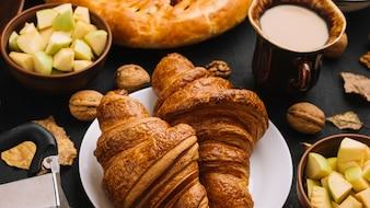 Croissants in der Nähe von Äpfeln und Milch