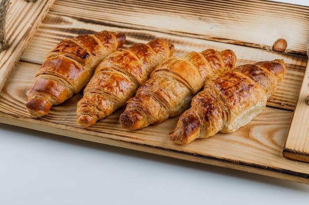 Croissants in einem holztablett.