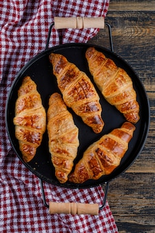 Croissants in einer pfanne auf holz- und küchentuch. flach liegen.