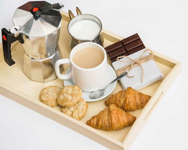 Croissants, kekse, schokolade, tee und milch auf tablett