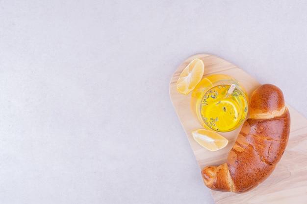 Croissants mit einem glas limonade auf weißer oberfläche