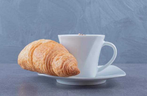 Croissants mit einer tasse tee. auf grauem hintergrund.