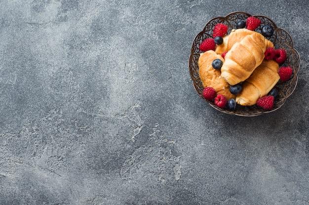Croissants mit frischen himbeeren und heidelbeeren
