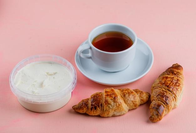 Croissants mit frischkäse, tee auf rosa tisch,