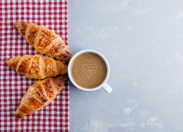 Croissants mit kaffee auf gips und picknicktuch, flach liegen.