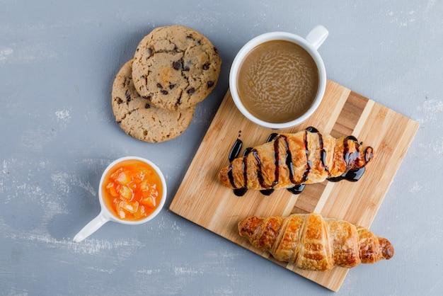 Croissants mit kaffee, keksen, sauce flach auf gips und holzbrett liegen