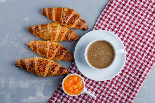 Croissants mit kaffee, sauce flach auf gips und picknicktuch liegen