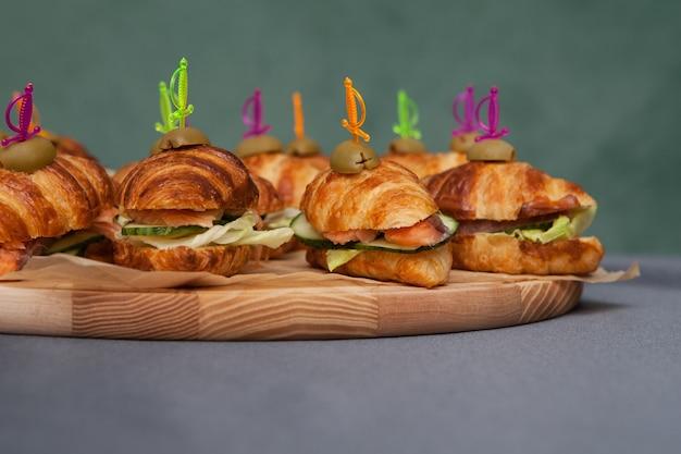 Croissants mit lachs und frischem gemüse auf einem holzschneidebrett.