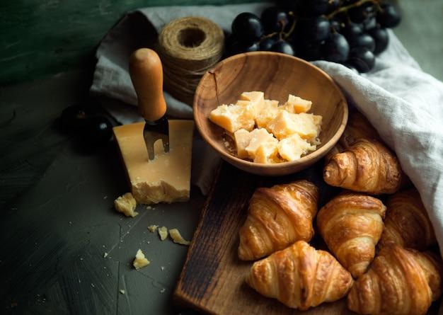 Croissants mit leckerem käse und trauben für ein leckeres frühstück. original leckere französische croissants mit käse und trauben auf dem holztisch. butterflocken-wiennoiserie-brötchen markanter halbmond