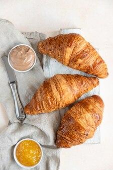 Croissants mit marmelade und schokoladencreme, heller betonhintergrund. selektiver fokus. ansicht von oben.