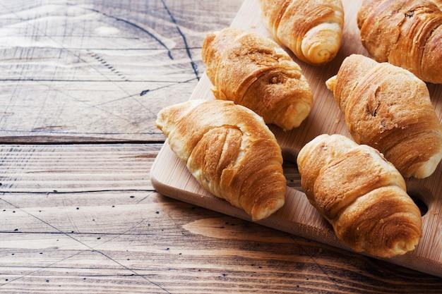 Croissants mit schokoladenfüllung auf hölzernem hintergrund. speicherplatz kopieren.