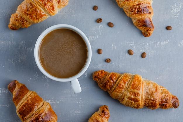 Croissants mit tasse kaffee, kaffeebohnen, flach liegen.