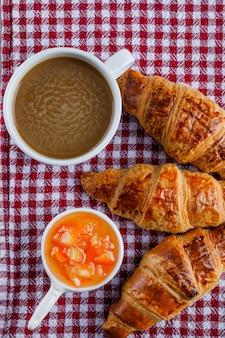 Croissants mit tasse kaffee, sauce auf picknicktuch, flach liegen.