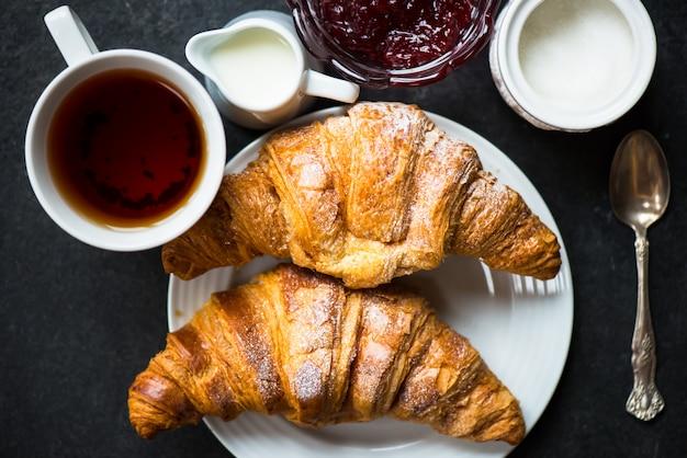 Croissants mit zuckerguss, tasse tee, milch, zucker und erdbeermarmelade