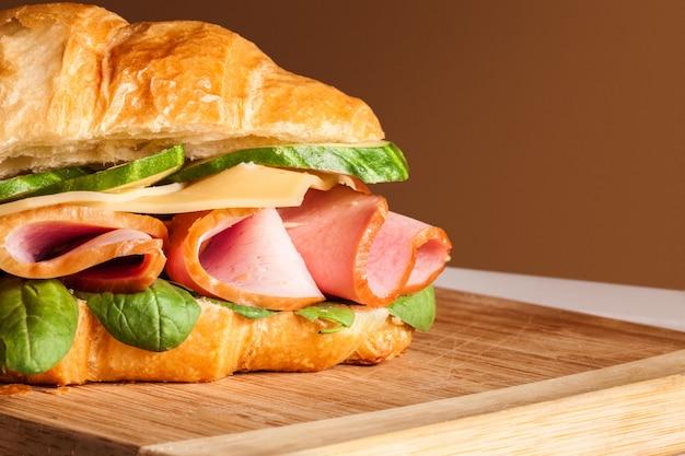 Croissants sandwiches auf dem holzschneidebrett