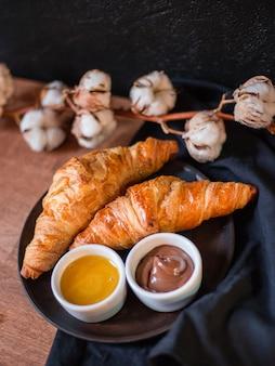 Croissants, schokolade und honig. woden platte mit köstlichem frühstück, baumwollblume