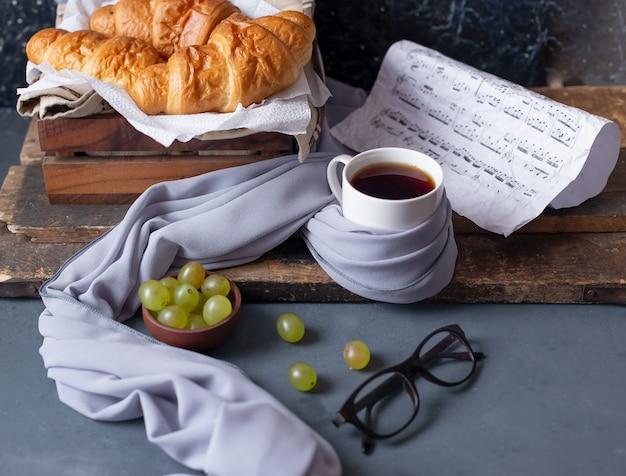 Croissants, trauben und eine weiße tasse tee