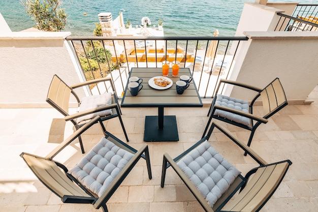 Croissants und frisch gepresste saftgartenmöbel auf dem balkon mit blick auf das meer