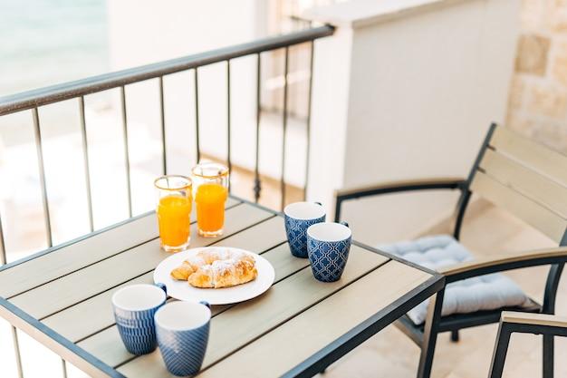 Croissants und frisch gepresster saft, gartenmöbel auf dem balkon mit blick auf das meer. hochwertiges foto