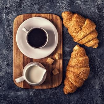 Croissants und kaffee auf einem dunklen hintergrund