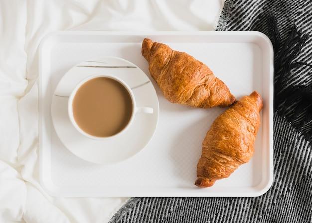 Croissants und kaffee flach auf tablett legen