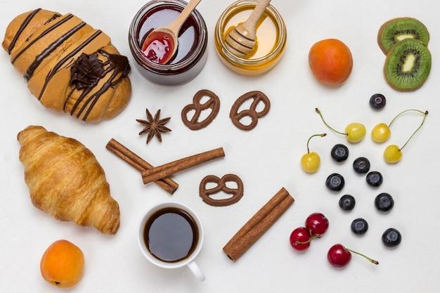 Croissants und kekse, beeren, aprikosenhonig, marmelade, zimt. set von produkten für ein nahrhaftes frühstück. weiße oberfläche. flach liegen