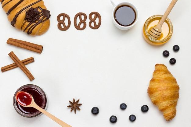 Croissants und kekse, beeren, aprikosenhonig, marmelade, zimt. set von produkten für ein nahrhaftes frühstück. weißer hintergrund. flach liegen. speicherplatz kopieren