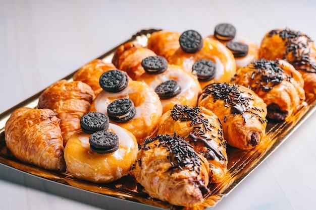 Croissants und schokoladendonuts zum frühstück süße snacks auf dem tisch