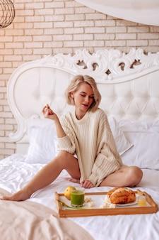 Croissants und smoothie. schlanke frau, die auf einem großen weißen bett sitzt und leckere croissants und grünen smoothie betrachtet