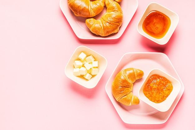 Croissants zum frühstück auf einem rosa hintergrund, draufsicht,