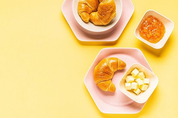 Croissants zum frühstück auf gelbem hintergrund, draufsicht