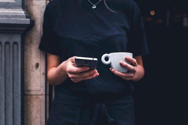 Crop barista mit getränk mit smartphone