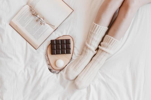 Crop beine in der nähe von schokolade und buch auf dem bett