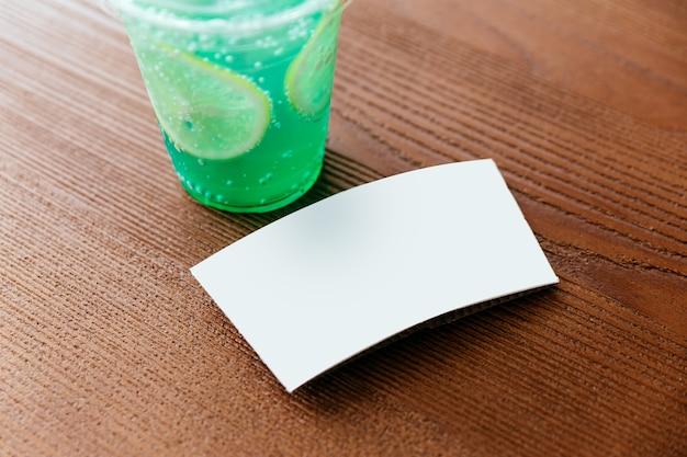 Crop bild der weißen tasse hülse von grün gefrorenem soda mit geschnittener zitrone auf einem holztisch.