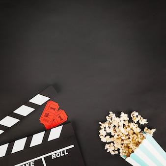 Crop clapperboard in der nähe von tickets und popcorn